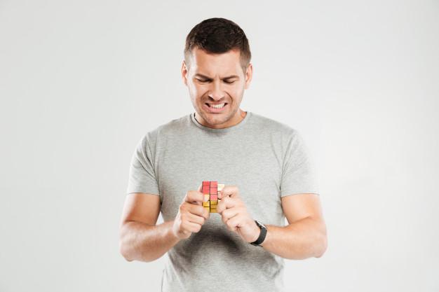 pria bingung menyelesaikan Kubus Rubik