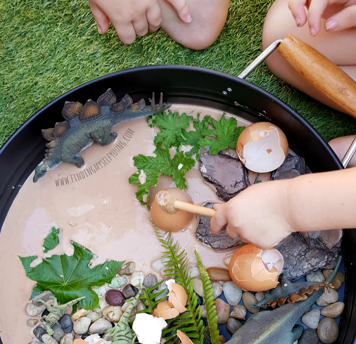 Children hitting egg shells in dinosaur play tray