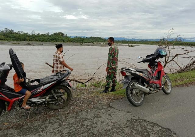 Tanggap Bencana, Sertu Ruslan Bersama Warga Terus Pantau Luapan Air Sungai