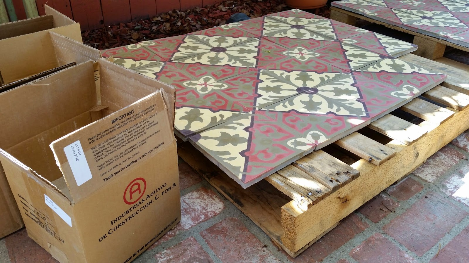 Cement tiles are removed from the box and placed on pallets prior to applying the sealer.
