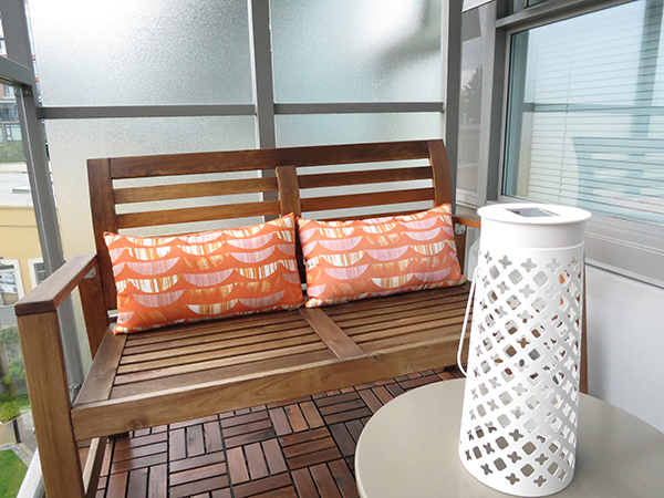 Vancouver city condo apartment small space patio makeover: IKEA Applaro bench and Solvinden white LED solar-powered table lamp, West Elm orange lumbar support cushions
