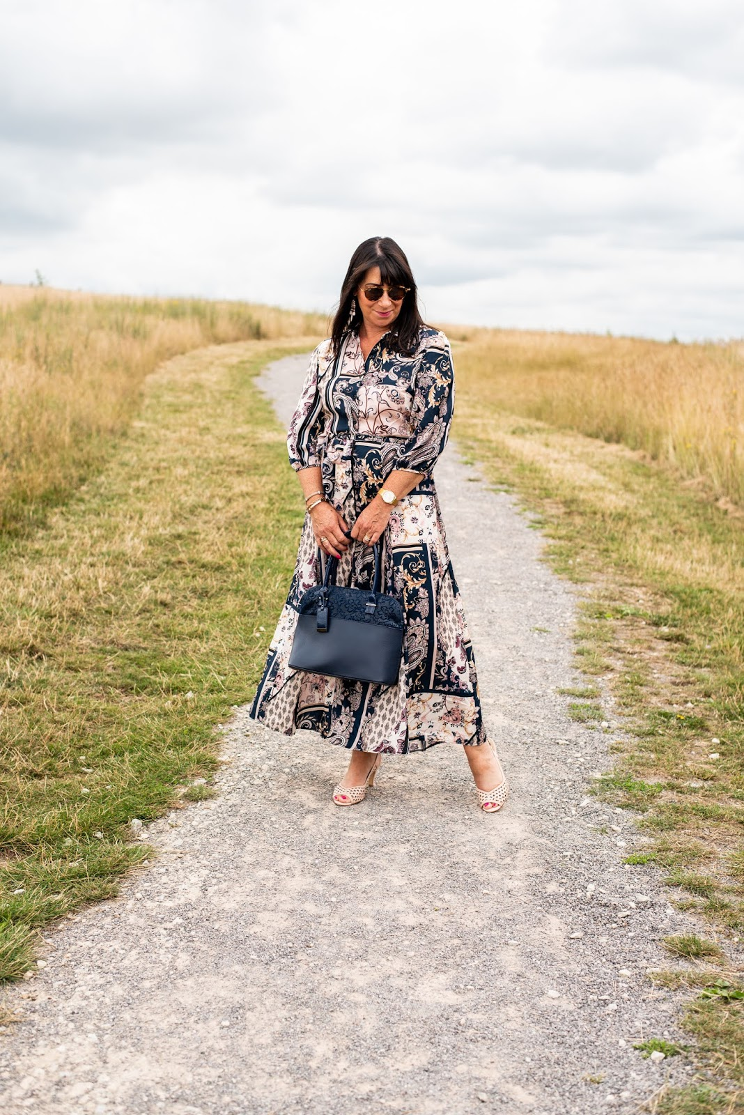 In the Signature Color challenge Jacqui Berry has chosen a pink and dark blue print dress and paired it with a blue bag and pale pink sling back shoes.