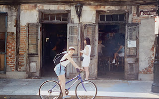 Pamela P. Roselli stops her bike on Bourbon Street in front of Lafitte's Bar (c. 1990s)