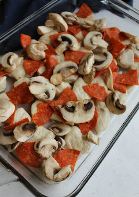 biscuits with pepperoni and mushrooms in pan ready to turn into pizza casserole bake
