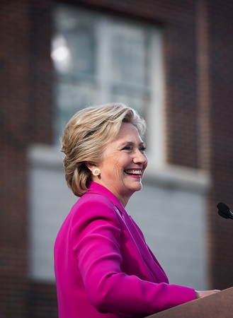 image of Hillary Clinton in a pink blazer, standing at a podium, smiling