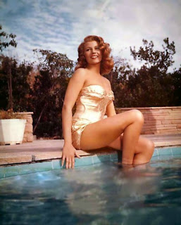Rita Hayworth posed at edge of swimming pool wearing gold swimsuit from the 1950's