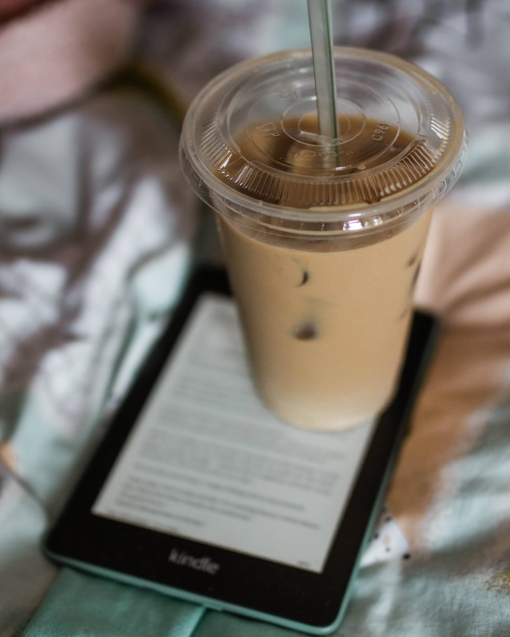 iced coffee latte sitting on top of kindle paperwhite