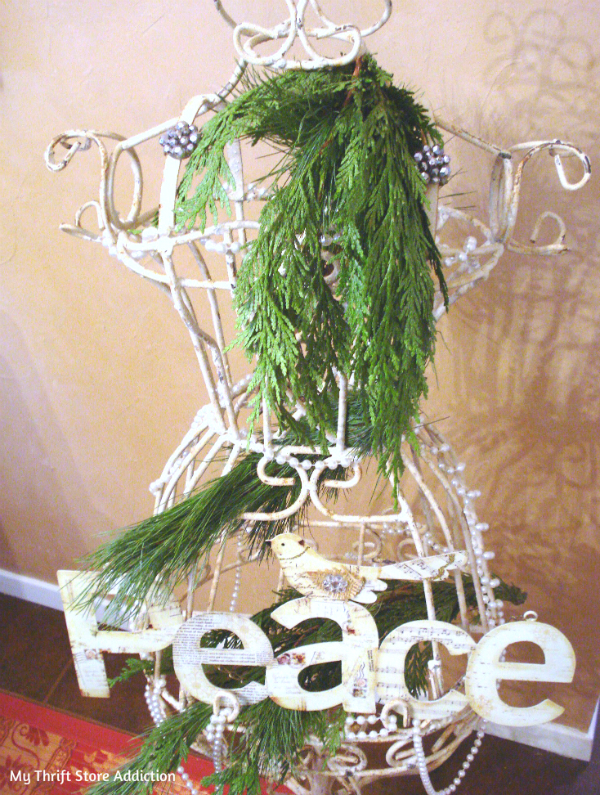 Dress form adorned in Xmas greenery