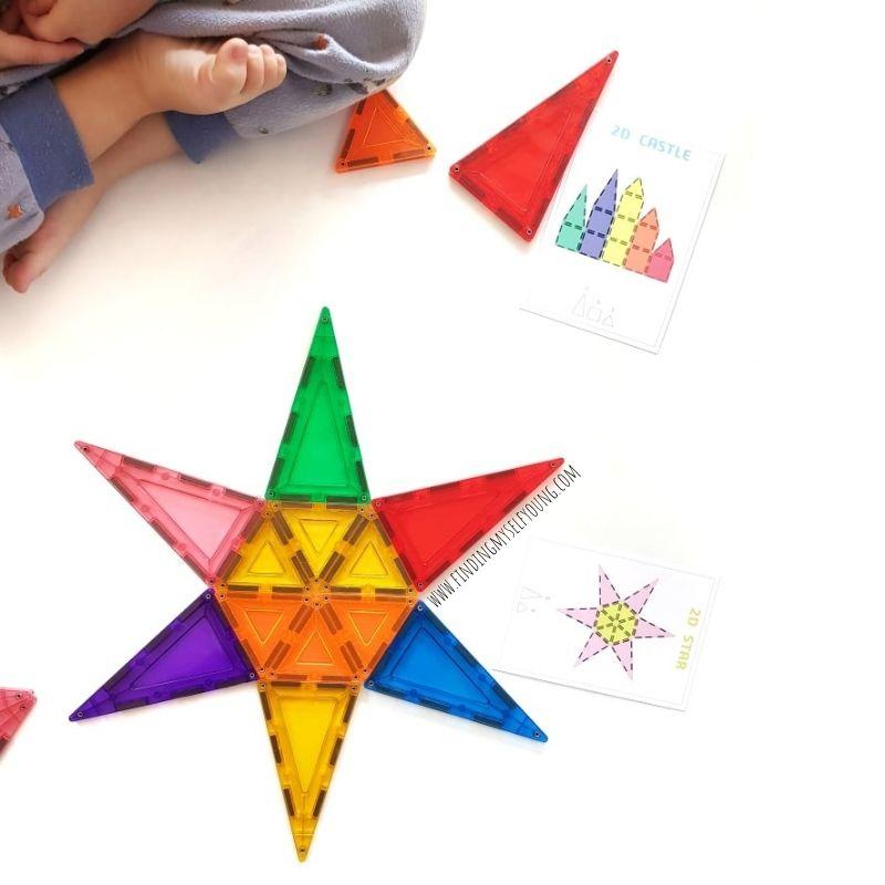 preschooler building magnetic star using magblox challenge cards