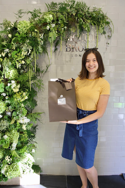 Abbey, wearing a denim skirt and striped top, holds a Molton Brown goodie bag in front of the store's sign