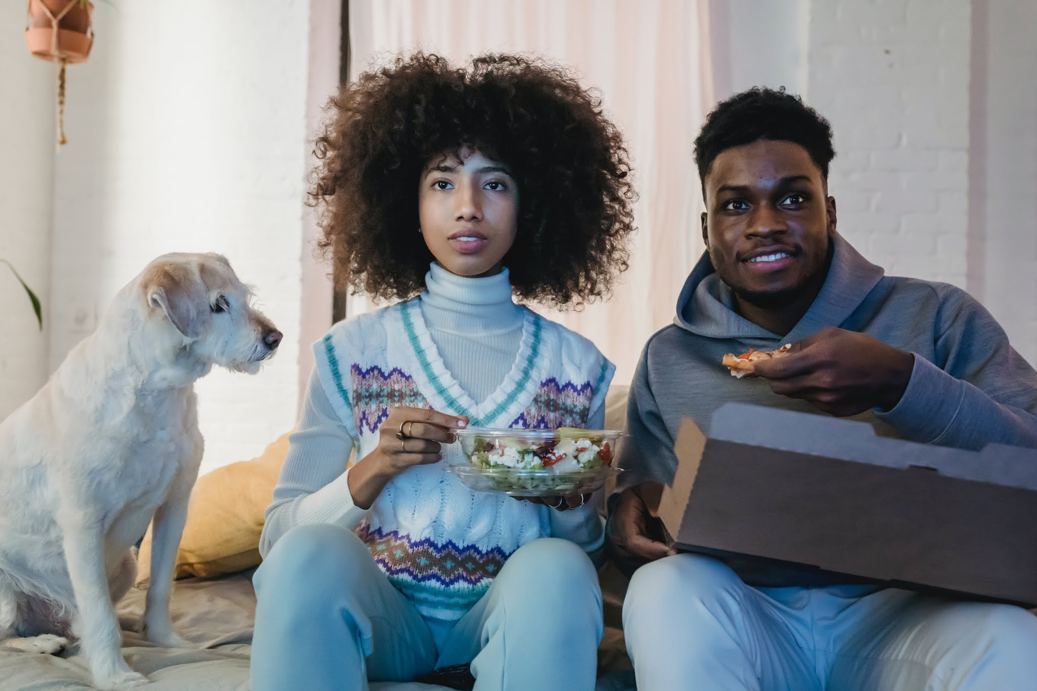 Two adults eating popcorn and watching TV with dog. Photo by Andres Ayrton from Pexels