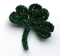 A dark green shamrock crocheted from sparkly metallic yarn on a white background.