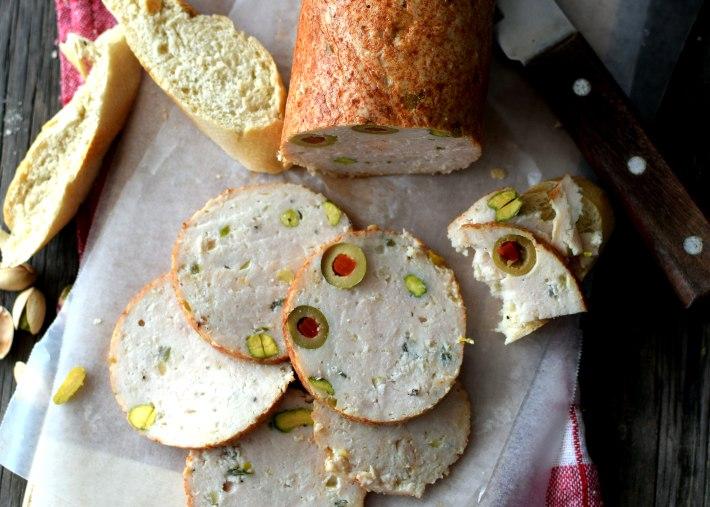 Fiambre o jamón de pollo casero, servido en una tabla de madera, cortado en rodajas acompañado de pan y vino