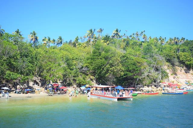 embarcacao de turistas atracando em uma pequena faixa de areia