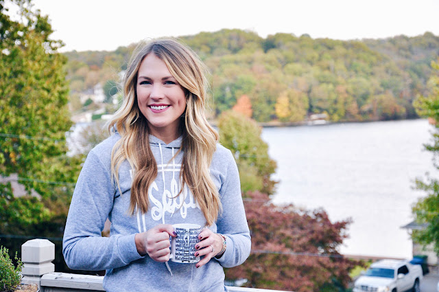 happy girl with mug of cider by the lake