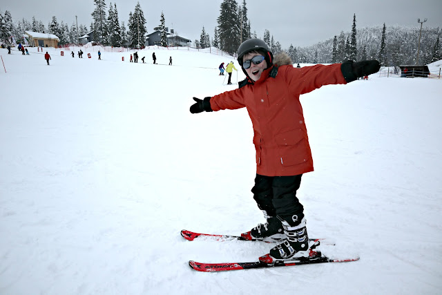 Boy in full ski outfit posing on the slopes.