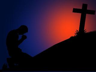 hombre orando de rodillas frente a una cruz