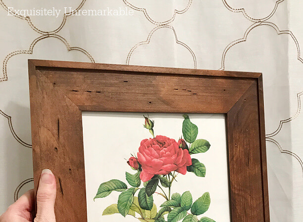 Framed rose print held up to a shower curtain in the bathroom