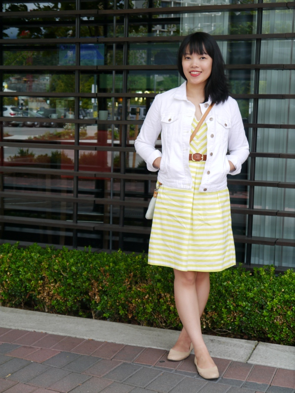 Vancouver blogger Lisa Wong of Solo Lisa wears a yellow and white striped day dress with a white denim jacket, nude ballet flats, and little blue crossbody bag.