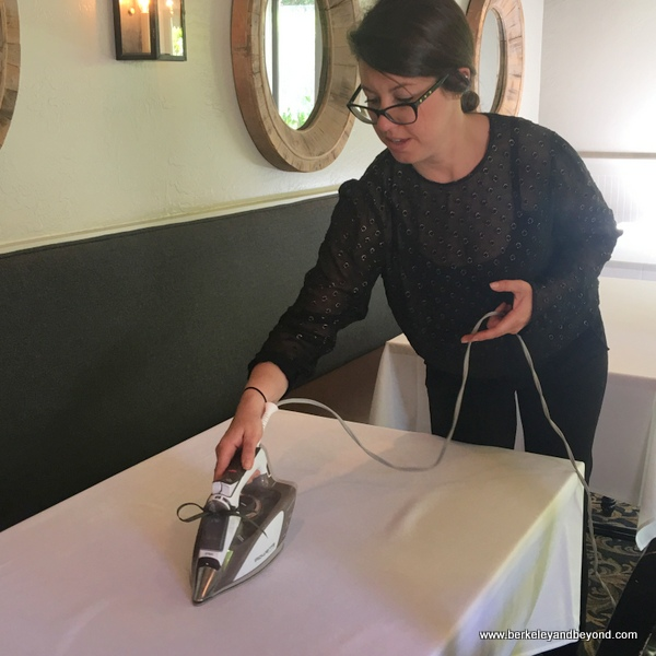 employee ironing tablecloth at The Farmhouse Inn restaurant in Forestville, California