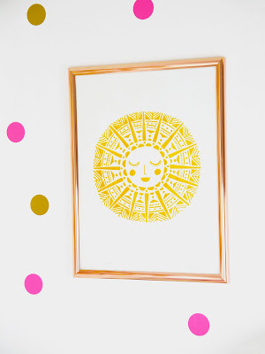 a white wall with pink and gold poka dots, and a copper frame with a mustard smiling sun print