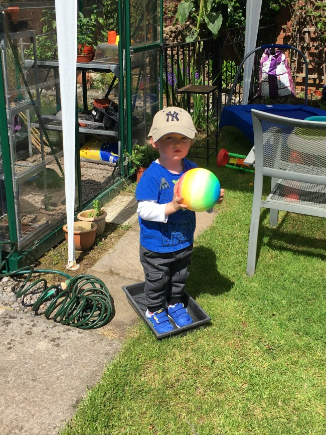 toddler-stood-in-plant-tray-holding-ball-with-NY-cap-on