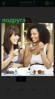 две подруги за столиком в кафе обсуждают и едят мороженное