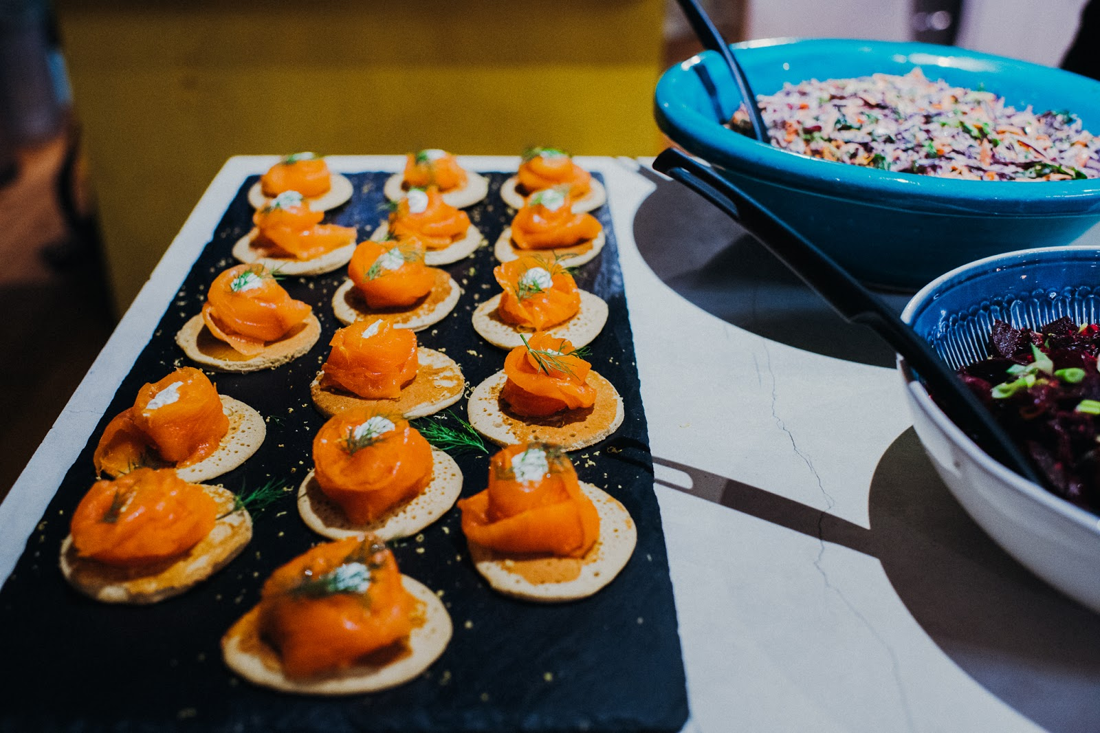 Rows of smoked salmon rolled onto savoury pancakes.