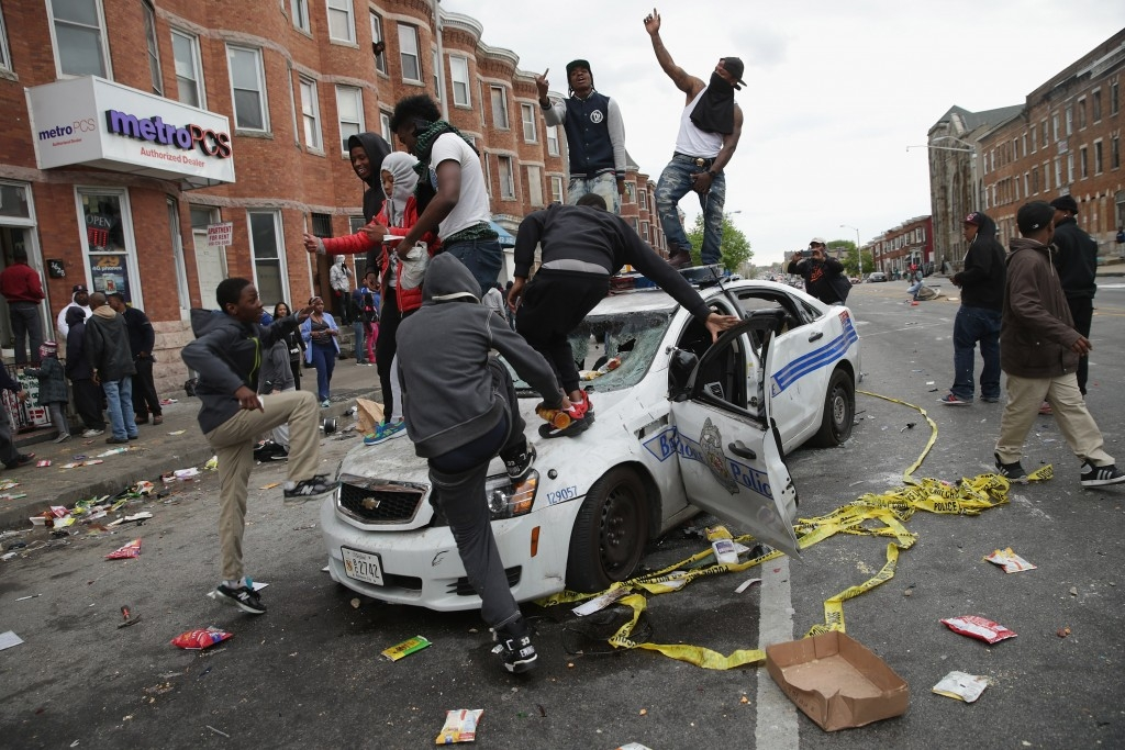 70 Of The Most Touching Photos Taken In 2015 - Demonstrators climb on a destroyed Baltimore Police car during violent protests following the funeral of Freddie Gray.
