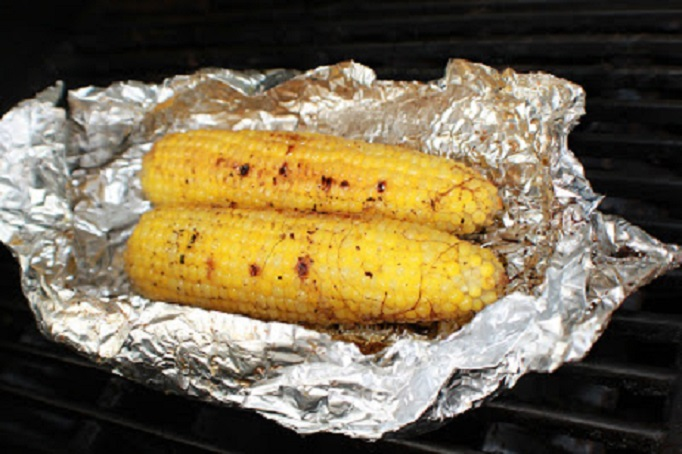 how to cook corn on the cob, this is grilled and on an aluminum foil wrapped corn with tongs for serving