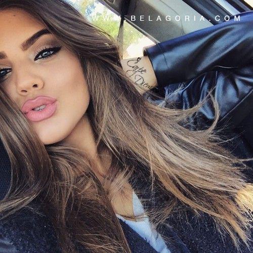 Selfie de una bella modelo en su auto, lleva tatuaje de carpe diem en la muñeca