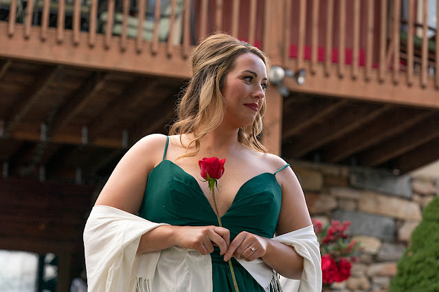 Bridesmaid in emerald dress with a red rose in hand Magnolia Farm Asheville Wedding Photography captured by Houghton Photography