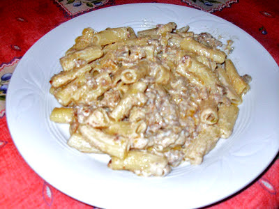 Plato de macarrones con carne y paté cubiertos con salsa de queso Roquefort