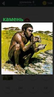 около воды сидит древний человек с камнем в руках