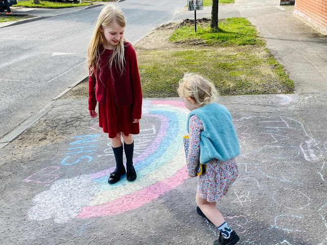walking on a chalk rainbow on the pavement with a thank you NHS message on our daily allowed exercise to take a break from school
