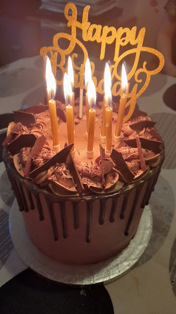 A 6 round chocolate cake with chocolate dripping and lit candles sits onna brown dinner table