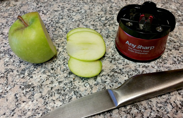 The AnySharp knife sharpener, a knife and a chopped apple.