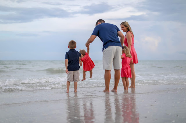 family walking in the water on sanibel