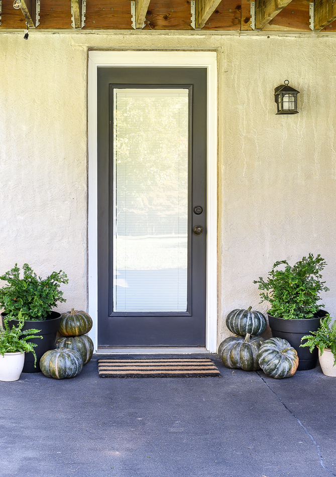 Fall patio decor with pumpkins and ferns