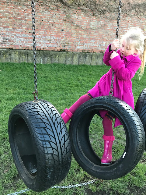 A 5 year old girl climbing on some tyres as part of an assault course