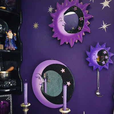 Three purple and black moon-mirrors mounted on a rich, deep purple wall. The wall has some gold and silver stars stencilled on it visible in the top left. The top-most mirror is bright purple and depicts a man-in the moon with a halo of purple rays tipped with gold. There is a black section on the right of the crescent with three stars. It is medium sized. The middle mirror is to the right; it is a blueish purple and is the same crescent moon with halo of rays design, but much smaller and a bluer colour, again with three stars. Hanging off the small moon mirror is a filigree silver moon-pendant with simulated circular stone. The lower mirror is a large light purple mirror of just a crescent moon on a circular background, and there are three stars; the background is black. There is less gold. To the left there is a black gloss corner unit of shelves; on the bottom shelf is visible a black stone box with Celtic knotwork supporting a brass Nepalese singing bowl with wooden striker. On the middle shelf is visible a resin figure of a wizard wearing a blue robe with purple and gold and holding a staff; the wizard has long white hair, a beard and a hat. Next to the wizard, on the far left, a snowglobe is partiall in view, half of it cropped at the edge of the image. The snow-globe is a clear globe on a black turned pedestal and inside is a graveyard scene made of metal. The items on the top-most shelf are obscured, but part of a metallic foil print of a unicorn is visible - just the lower hooves and some of a purple night sky. A dark purple glittery skull, very small, is also just about visible but obscured by shadow. In the foreground there are two purple rolled-beeswax candles in silver old-fashioned Classical candle-sticks. The photograph is taken in daylight, and the lighting is neutral.
