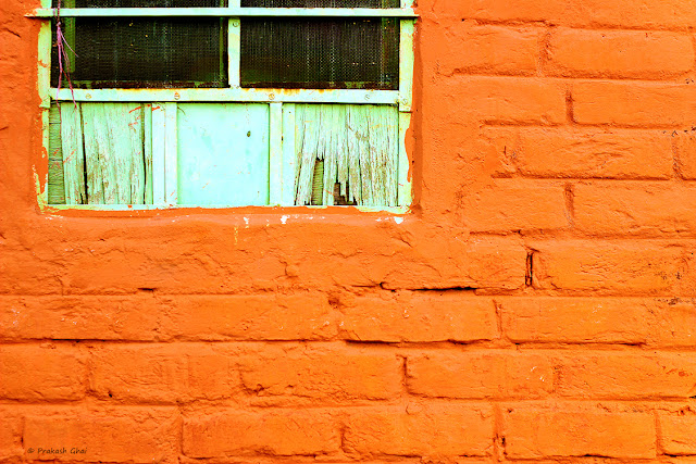 A minimalist photo of a Green window on an orange colored brick wall.