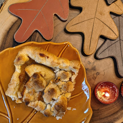 Slice of caramel apple slab pie displayed on fall leaf plate with fall decor