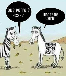 Charge. No pasto, duas zebras conversam. Elas são parecidas e brancas. A da esquerda tem listras pretas como de um código de barras, e um tufo de capim na boca; a outra, tem no lombo, um QRCode em preto. A zebra listrada pergunta: Que porra é essa? Resposta: Upgrade cara!