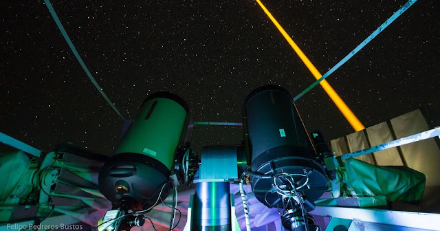 The experiment on La Palma: The laser beam (yellow) generates an artificial guide star in the mesosphere. This light is collected in the receiver telescope (front left). The laser source and the receiver telescope are eight meters away from each other. Credit: Felipe Pedreros Bustos