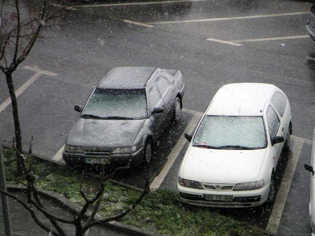 A neve a cair sobre os carros estacionados por trás da nossa casa em Portugal.