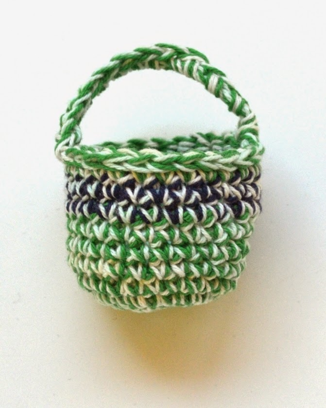 Mini crocheted basket with main colour green/variegated mint and navy/variegated mint contrast stripe (horizontal)