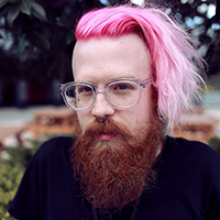 Adam Koebel portrait. Pink hair, bearded, bespectacled man