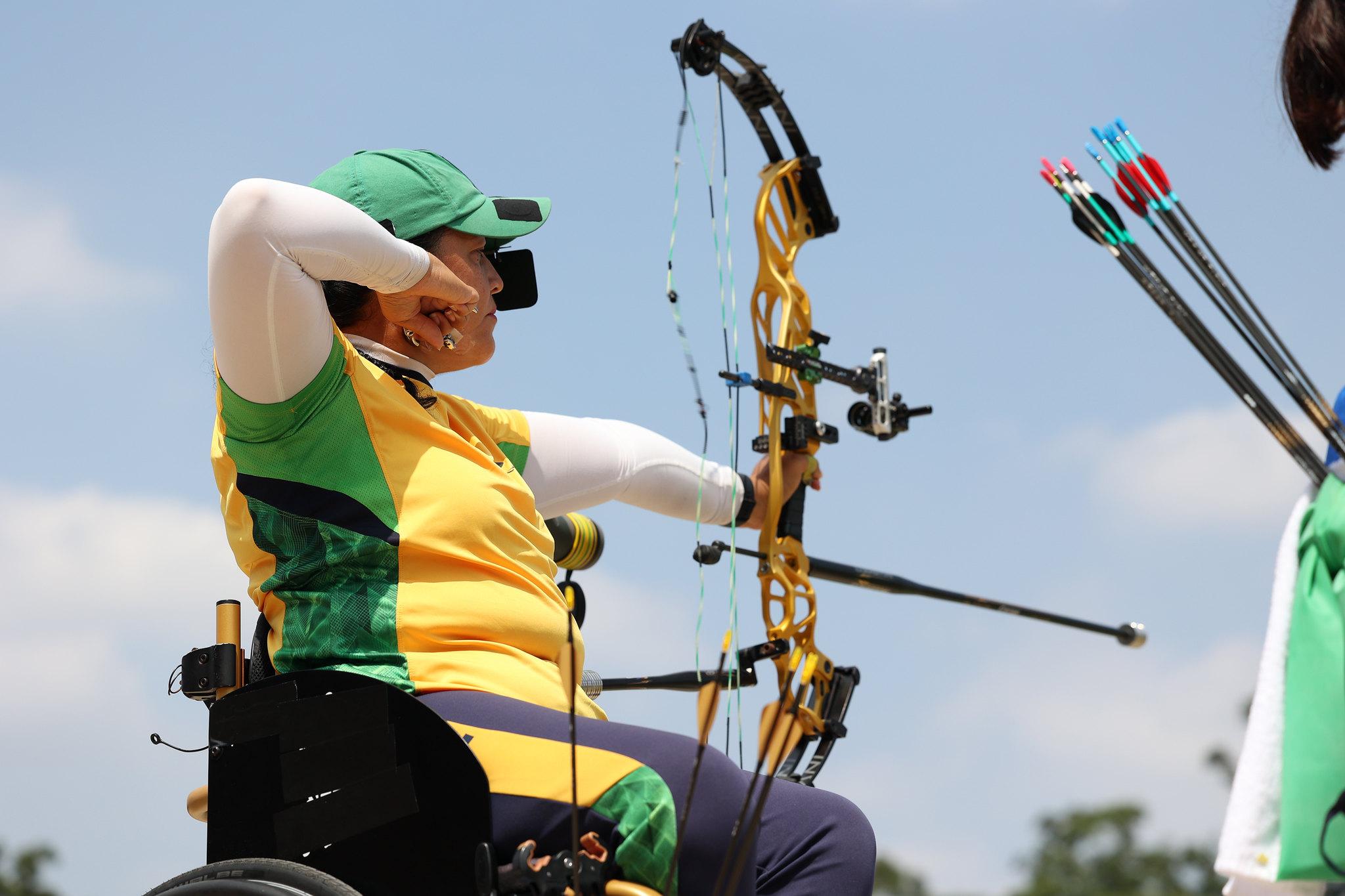 Jane Karla Gögel com uniforme do Brasil prepara arco e flecha