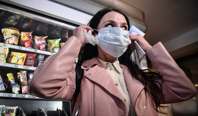 A woman buys a face mask in a vending machine in the subway in Moscow amid the spread of the COVID-19 coronavirus. Photo: AFP
